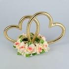 Кольца в форме сердца на подставке из кремовых цветов