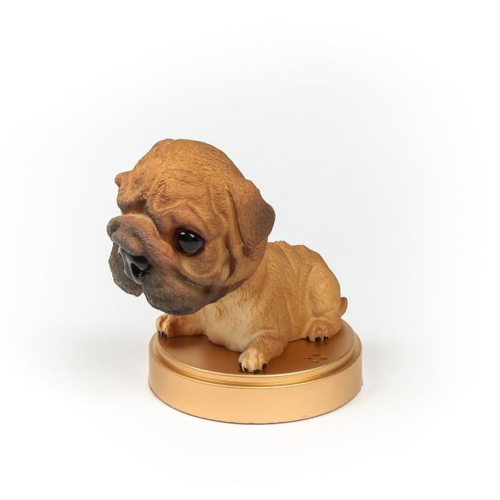 Собака на панель авто, качающая головой, мопс