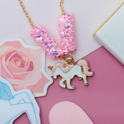 """Pendant baby """"Vibracula"""" sequins, a unicorn, the color pink and white gold"""