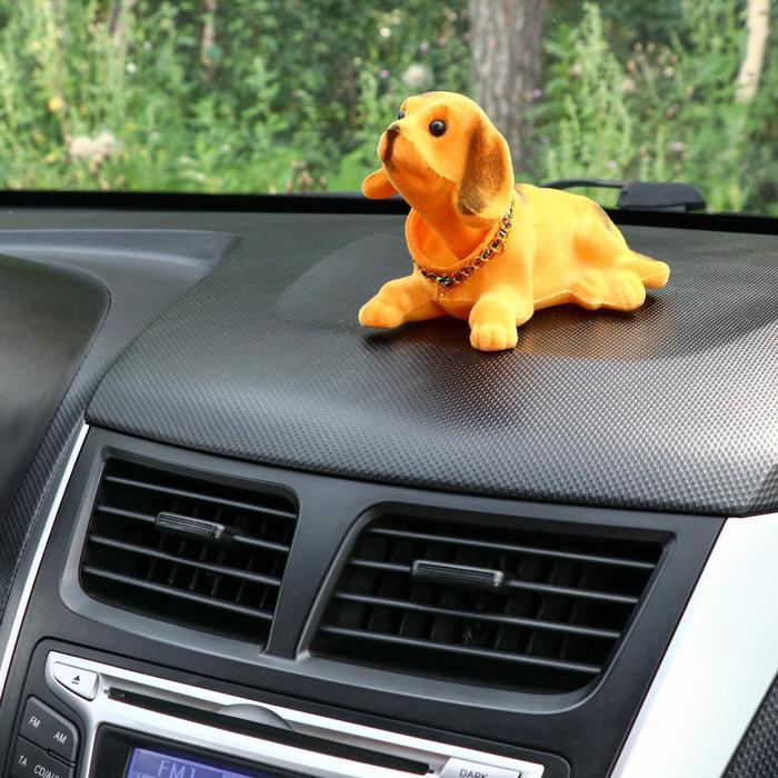 Собака на панель авто, качающая головой, большая, коричневый окрас