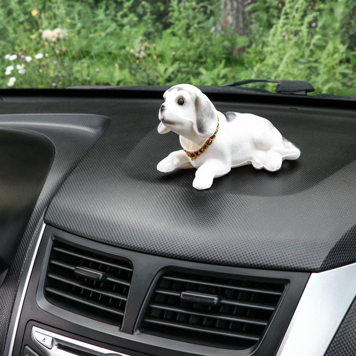 Собака на панель авто, качающая головой, большая, белый окрас