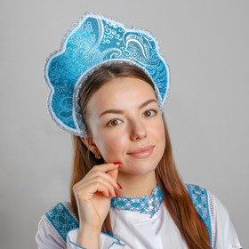 The headdress is blue with silver braid